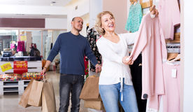 Man with bags waiting for woman selecting dress Stock Images