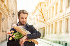 Man with baguette, and flower bouquet looking at watch Stock Photography