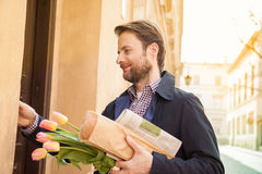 Man with baguette, newspaper and flower bouquet ringing doorbell Royalty Free Stock Image