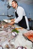 Man bak räknare klippt av stycke av fisken Royaltyfria Foton