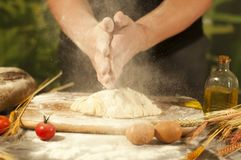 Man baker hands,pizza  kneads dough and making housework making bread, butter, tomato flour. Man baker hands, kneads dough and making bread butter tomato flour Royalty Free Stock Image