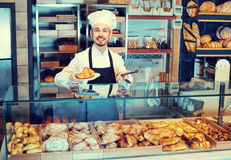 Man baker showing warm tasty croissant. Smiling diligen man baker showing warm tasty croissant in bakery Royalty Free Stock Photography