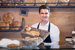 Man bakery employee offering bread and pastry. Man bakery employee offering bread and different pastry for sale Royalty Free Stock Photography