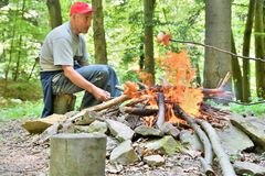 Man baking the sausage on natural flames in the forest bonfire royalty free stock photography