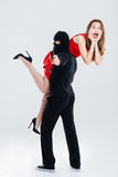 Man in balaclava stealing woman and pointing gun on you Stock Photos
