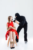 Man in balaclava threatening by gun to bounded woman Stock Image