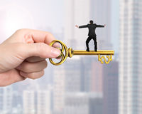 Man balance on treasure key in dollar sign shape Stock Images
