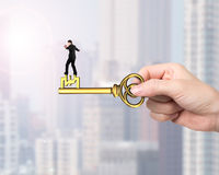 Man balance on treasure key in pound sign shape. With hand holding, on city buildings background stock photos