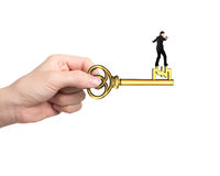 Man balance on treasure key in pound sign shape. With hand holding, on white background stock photo