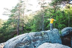 A man balances on a stone. The guy goes down the stone slope and tries not to fall. Traveling through picturesque places. A man in the background of a forest Stock Photo