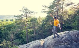 A man balances on a stone. The guy goes down the stone slope and tries not to fall. Traveling through picturesque places. A man in the background of a forest Royalty Free Stock Images