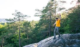 A man balances on a stone. The guy goes down the stone slope and tries not to fall. Traveling through picturesque places. A man in the background of a forest Royalty Free Stock Image