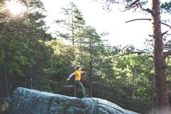 A man balances on a stone. The guy goes down the stone slope and tries not to fall. Traveling through picturesque places. A man in the background of a forest Stock Image