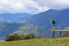 Man balancing in Baños, Ecuador. Man balancing in a piece of wood over the mountains of Baños, Ecuador stock photo