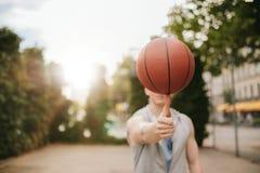 Man balancing basketball on his thumb. On outdoor court. Streetball player spinning the ball. Focus on basketball Stock Photo