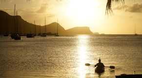 Man balancing a beer on top of his head in a kayak in the Tobago Cays, Saint Vincent and the Grenadines, Caribbean.