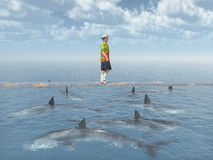 Man balancing on a board over the ocean with great white sharks Stock Image