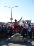 Man balancing on a board on a roller pin in front of crowd of to. SAN FRANCISCO - OCTOBER 11: British Circus performers put on a show at San Francisco Fisherman' Stock Images