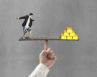 Man balancing with bullion on board Royalty Free Stock Photos