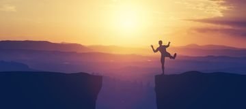 Man balancing on the edge of a cliff. stock photos