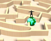 Man balancing on globe in wooden maze game Royalty Free Stock Photo