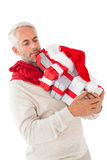 Man balancing many christmas gifts in his hands. On white background royalty free stock photo