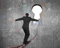 Man balancing on old iron chain toward keyhole with cityscape Stock Photography