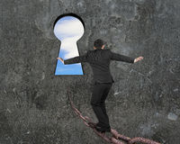 Man balancing on old iron chain toward keyhole with sky Stock Photo