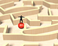 Man balancing on red ball in wooden maze game. Stock Photos