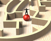 Man balancing on red ball in wooden maze game. Royalty Free Stock Photography