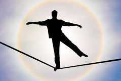 Man balancing on the rope challenge and risk taking concept Stock Photography