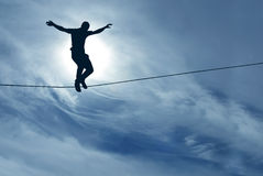 Man balancing on the rope concept of challenge and risk taking. Silhouette of man balancing on the rope concept of risk taking Stock Photography