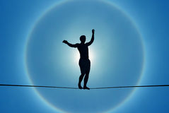 Man balancing on the rope concept of challenge and risk taking. Silhouette of man balancing on the rope concept of risk taking Stock Images