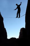 Man balancing on the rope concept of risk taking and challenge. Silhouette of man on the rope concept of risk taking vertical image Royalty Free Stock Images