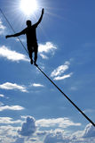 Man balancing on the rope concept of risk taking. Silhouette of a man on the rope risk taking and challenge concept Stock Photography