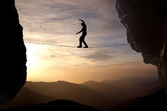 Man balancing on the rope concept of risk taking. Silhouette of man on the rope concept of risk taking and challenge Royalty Free Stock Photo