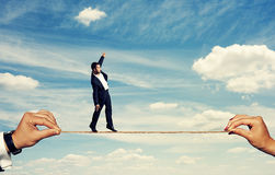 Man balancing on the rope over blue sky Stock Photos