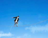 Man balancing on rope with sky. Man balancing on rope with blue sky background Royalty Free Stock Images