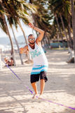 Man balancing on the rope. Teenage man balancing on slackline on the beach Royalty Free Stock Image