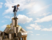 Man balancing on the tin cans Stock Photography