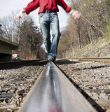 Man Balancing on Train Track. Man walking on a railroad track trying to maintain his balance royalty free stock photo