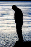 Man Balancing Water Silhouette. Man Balancing  on Water Silhouette is a capture of a man's sihlouette balancing on the end of a log over the waters of Puget Stock Image