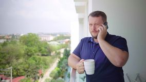 Man on the balcony drinking with a mug and talking on the phone stock photo