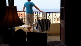 Man on the balcony overlooking the sea, woman on the bed, quarrel men and women stock video