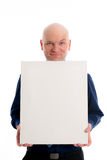 Man with bald head in is pointing to a canvas Royalty Free Stock Photos