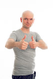 Man with bald head and thumbs up. Young man with bald head and thumbs up is looking friendly in to the camera Stock Photography