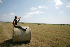 Man on bale with loudspeaker Stock Photos