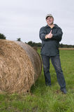 Man by the bale of straw vertical Stock Photography