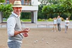 Man with ball for boule game. Smiling old men with ball for boule game in a city royalty free stock photography