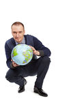 Man with ball-globe in position half squatting. Royalty Free Stock Photo